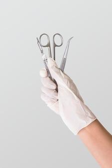 Gehandschoende hand met roestvrijstalen medische instrumenten