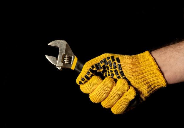 Gehandschoende hand met verstelbare moersleutel