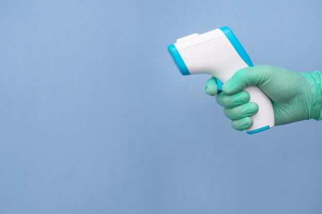 Gehandschoende hand van een gezondheidswerker die een thermometer vasthoudt die op blauw wordt geïsoleerd