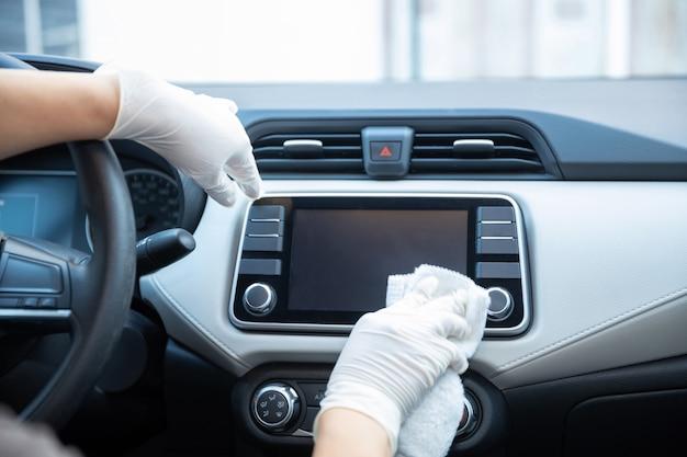 Gehandschoende handen die een auto schoonmaken
