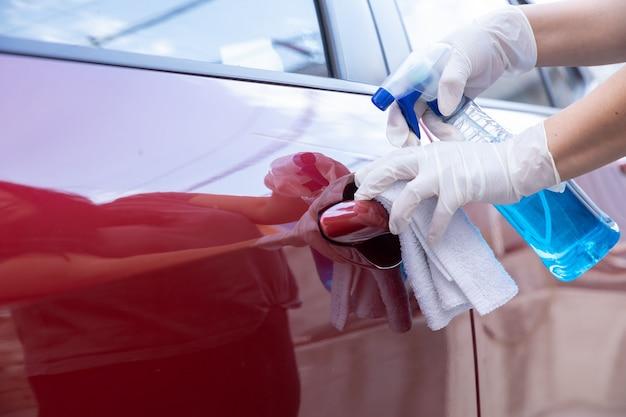 Gehandschoende handen die een autodeur schoonmaken wegens pandemie van het coronavirus