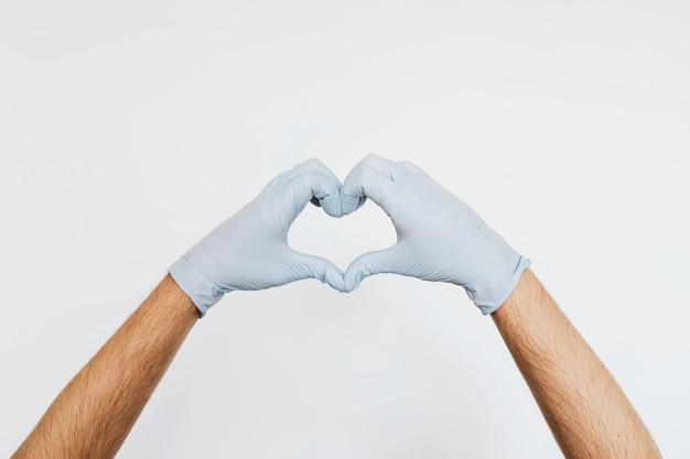 Gehandschoende handen maken een hartvormig bord op een grijze achtergrond
