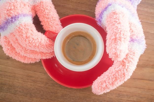 Gehandschoende handen met kopje koffie