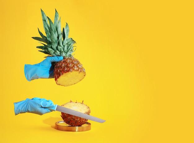 Gehandschoende handen snijden ananas in de helft op geel