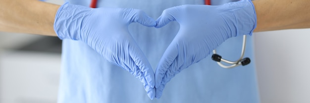 Gehandschoende handen van dokter zijn gevouwen in hart. medisch hulpconcept