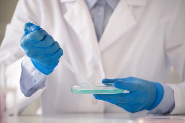 Gehandschoende handen van hedendaagse laboratoriummedewerker die pipet over petrischaal met blauwe vloeibare substantie houdt terwijl hij er een druppel van gaat nemen