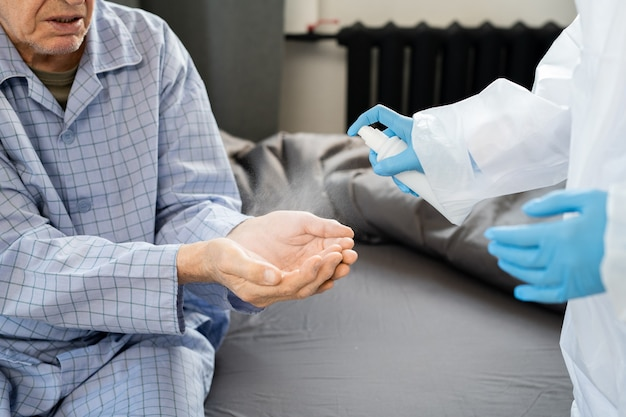 Gehandschoende handen van jonge dokter in beschermende overall die ontsmettingsmiddel sproeit op die van zieke senior man in blauwe pyjama die voor haar zit