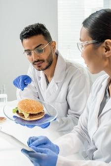 Gehandschoende mannelijke werknemer van voedselkwaliteitscontrole wijzend op hamburger met plantaardig vlees terwijl hij de kenmerken ervan beschrijft aan collega