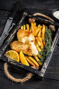 Gehavende fish and chips-schotel met frietjes en tartaarsaus in een houten dienblad