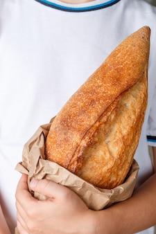 Geheel brood van vers gebakken tarwebrood in handen van kinderen
