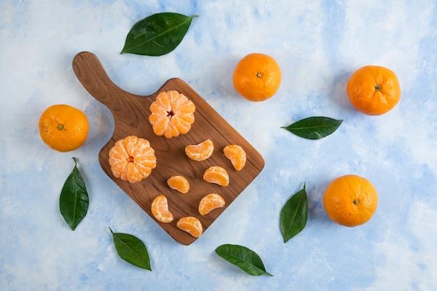 Geheel en gepeld plakje clementine mandarijnen. op een houten bord over blauw oppervlak