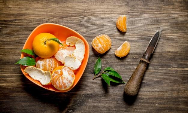 Geheel en gepelde mandarijnen in beker met bladeren en mes op houten tafel. bovenaanzicht