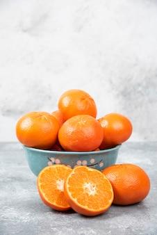 Geheel en plak sappig vers oranje fruit in een kom die op een steenlijst wordt geplaatst.