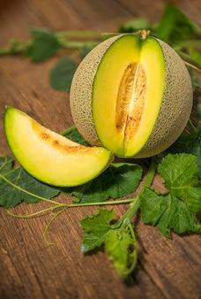 Geheel en plakje meloenen met bladeren op houten tafel, gele meloen of kantaloepmeloen met zaden geïsoleerd op houten tafel.