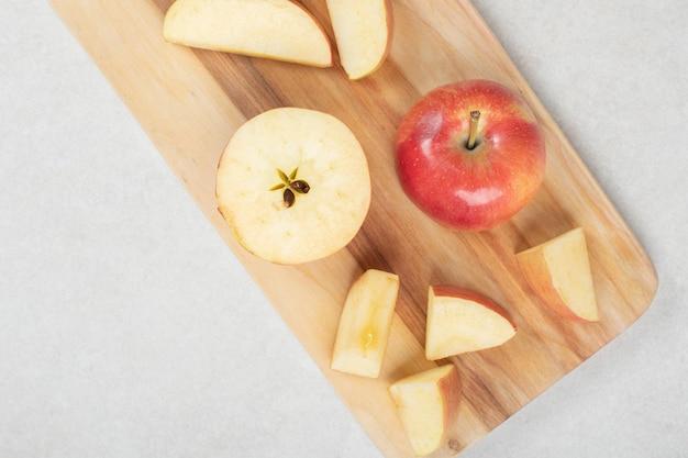 Geheel en plakjes rode appel op een houten bord