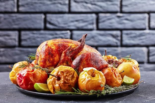Geheel gebraden kip geserveerd op een zwarte schotel met gebakken appels en aromatische kruiden op een betonnen tafel met een bakstenen muur