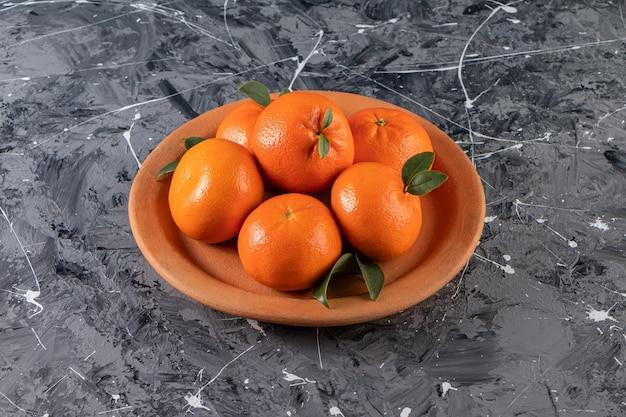 Geheel vers oranje fruit met bladeren die in kleiplaat worden geplaatst
