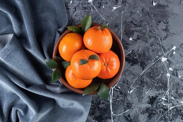 Geheel vers oranje fruit met bladeren die op een houten kom worden geplaatst