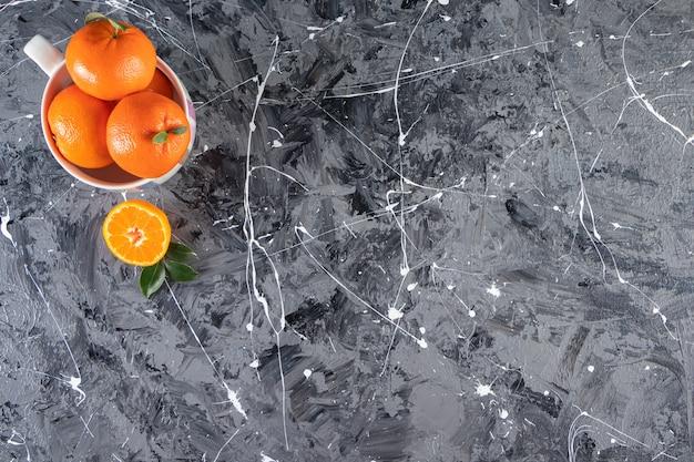 Geheel vers oranje fruit met bladeren in een witte kom.
