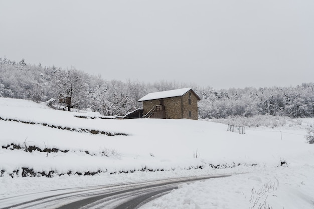 Geheel wit landschap bedekt met sneeuw en mist in noord-italië. rustiek stenen huis bedekt met sneeuw
