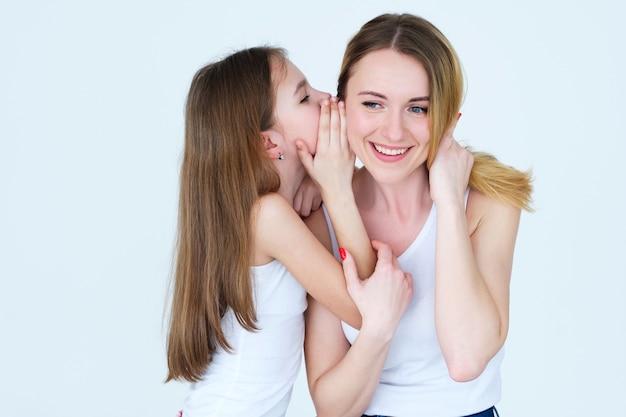 Geheim delen. dochter fluisterde iets in het oor van haar moeder.