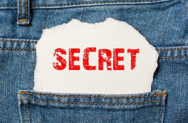 Geheim op wit papier in de zak van blauwe spijkerbroek