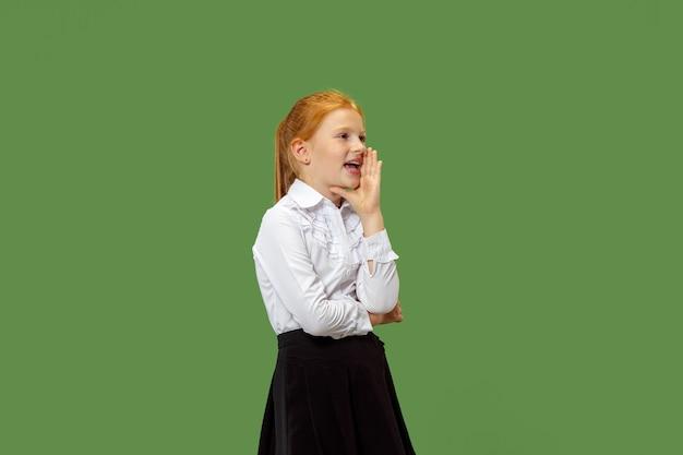 Geheim, roddelconcept. jong meisje dat een geheim achter haar hand fluistert. ze geïsoleerd op trendy groene studio achtergrond. jonge emotionele tiener. menselijke emoties, gezichtsuitdrukking concept.