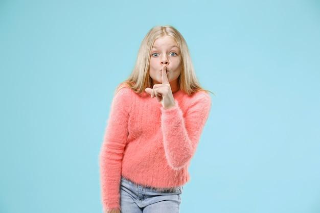 Geheim, roddelconcept. jong tienermeisje dat een geheim achter haar hand fluistert dat op trendy blauw wordt geïsoleerd