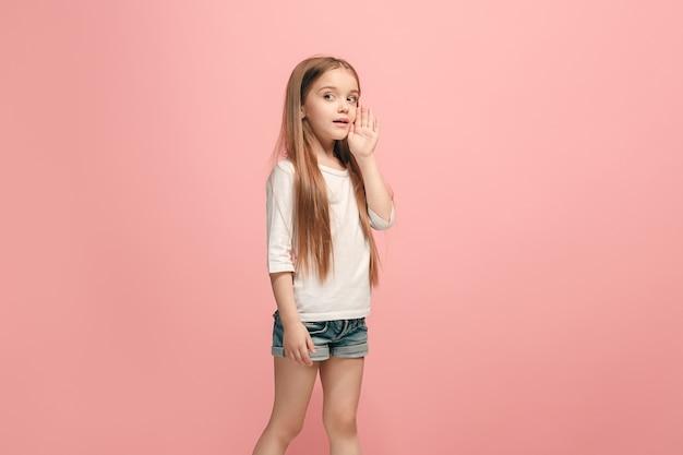 Geheim, roddelconcept. jong tienermeisje dat een geheim achter haar hand fluistert dat op trendy roze wordt geïsoleerd. jong emotioneel meisje