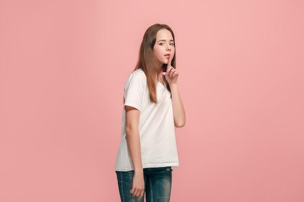 Geheim, roddelconcept. jong tienermeisje dat een geheim achter haar hand fluistert dat op trendy roze wordt geïsoleerd