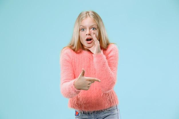Geheim, roddelconcept. jong tienermeisje fluisteren een geheim achter haar hand geïsoleerd op trendy blauwe studio achtergrond. jong emotioneel meisje. menselijke emoties, gezichtsuitdrukking concept.