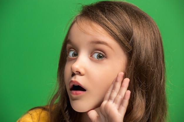 Geheim, roddelconcept. jong tienermeisje fluisteren een geheim achter haar hand geïsoleerd op trendy groene studio