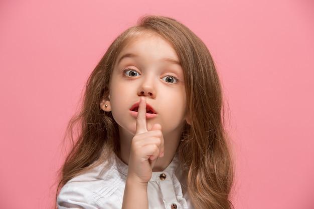 Geheim, roddelconcept. jong tienermeisje fluisteren een geheim achter haar hand geïsoleerd op trendy roze studio achtergrond. jong emotioneel meisje. menselijke emoties, gezichtsuitdrukking concept.