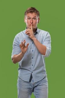 Geheim, roddelconcept. jonge man fluisteren een geheim achter zijn hand.