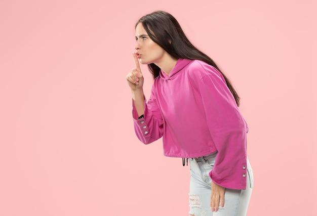 Geheim, roddelconcept. jonge vrouw fluistert een geheim achter haar hand. bedrijfsvrouw die op trendy roze muur wordt geïsoleerd. jonge emotionele vrouw. menselijke emoties, gezichtsuitdrukking concept.