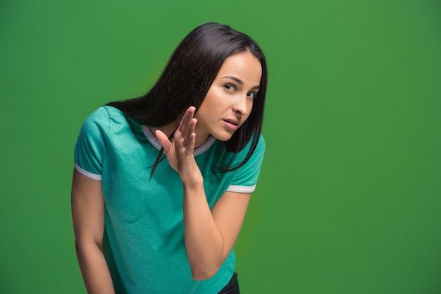 Geheim, roddelconcept. jonge vrouw fluistert een geheim achter haar hand. zakenvrouw geïsoleerd op trendy groene studio achtergrond. jonge emotionele vrouw. menselijke emoties, gezichtsuitdrukking concept.