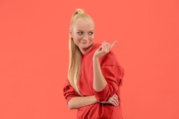 Geheim, roddelconcept. jonge vrouw fluistert een geheim achter haar hand. zakenvrouw geïsoleerd op trendy koraal studio achtergrond. jonge emotionele vrouw. menselijke emoties, gezichtsuitdrukking concept.