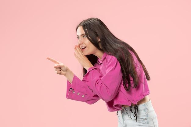 Geheim, roddelconcept. jonge vrouw fluistert een geheim achter haar hand. zakenvrouw geïsoleerd op trendy roze studio achtergrond. jonge emotionele vrouw. menselijke emoties, gezichtsuitdrukking concept.