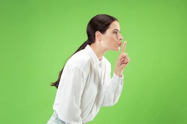 Geheim, roddelconcept. jonge vrouw fluistert een geheim achter haar hand.