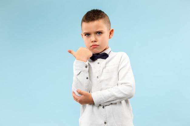 Geheim, roddelconcept. tienerjongen fluistert een geheim achter zijn hand. kind geïsoleerd op trendy blauwe studio achtergrond. menselijke emoties, gezichtsuitdrukking concept.