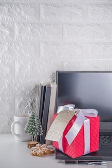 Geheime kerstman. kerstviering in kantoor. bureau met laptop, notitieblokken, kantoorbenodigdheden, smartphone en grote kerstcadeaudoos met feestelijke strik. flatlay