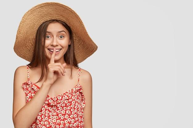 Geheime meid met een tevreden uitdrukking, lacht positief, deelt geheimen met goede vriend, vraagt het aan niemand te vertellen