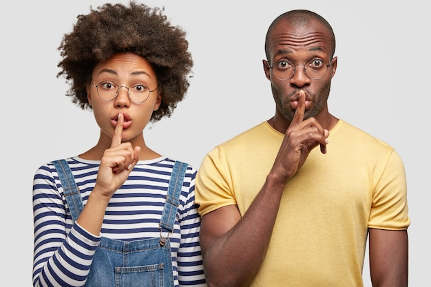 Geheime vrouw en man tonen stilte-teken, hebben verbaasde uitdrukkingen, raken lippen aan met wijsvingers