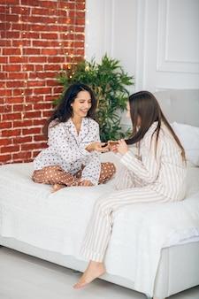 Geheimen delen. twee jonge meisjes in pyjama zittend op een bed en praten