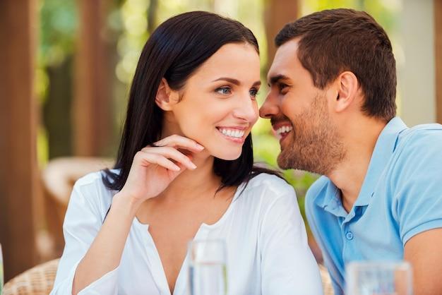 Geheimen met haar delen. knappe jongeman die iets aan zijn vriendin vertelt en glimlacht terwijl hij buiten samen aan tafel zit