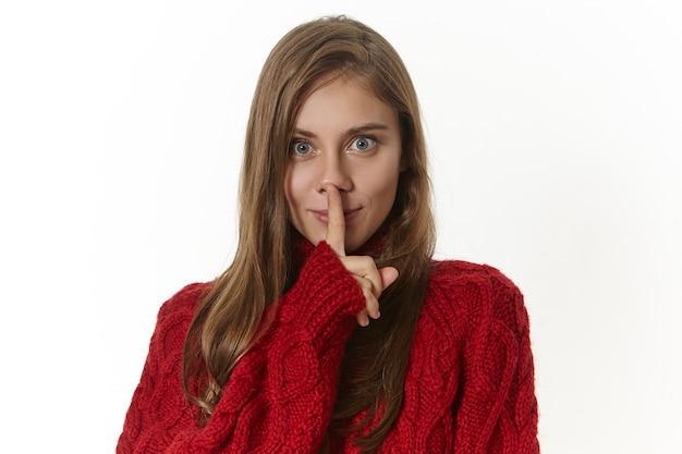 Geheimhouding, samenzwering en vertrouwelijke informatie concept. geïsoleerde afbeelding van aantrekkelijke mysterieuze jonge dame in trui shh geture met wijsvinger op de lippen maken, vragen om haar geheim te houden