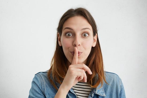 Geheimhouding, vertrouwelijkheid, privacy en samenzwering. portretvrouw die vinger op lippen houdt, met mysterieuze blik, vraagt om haar geheim niet weg te geven