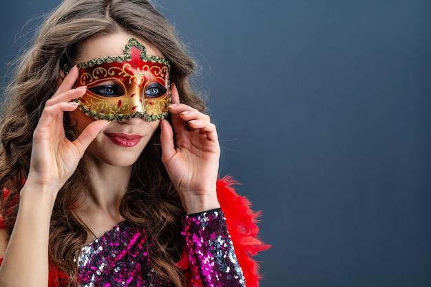 Geheimzinnige vrouw die carnaval-masker over blauwe achtergrond draagt