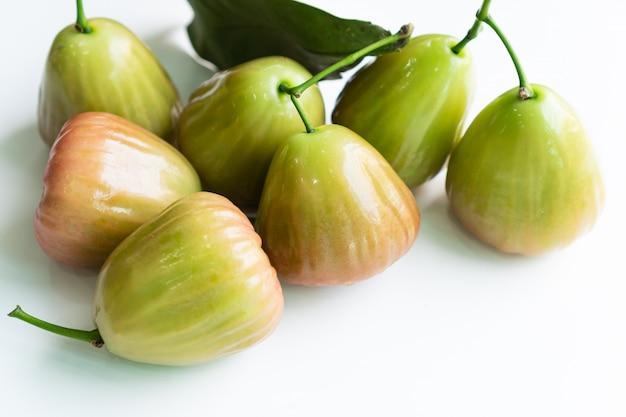 Gehele djamboevrucht met groen blad dat op wit wordt geïsoleerd