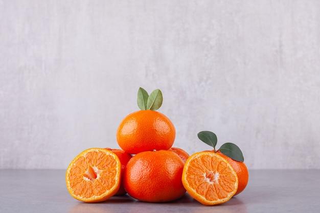 Gehele en gesneden mandarijnen met bladeren die op een steenachtergrond worden geplaatst.